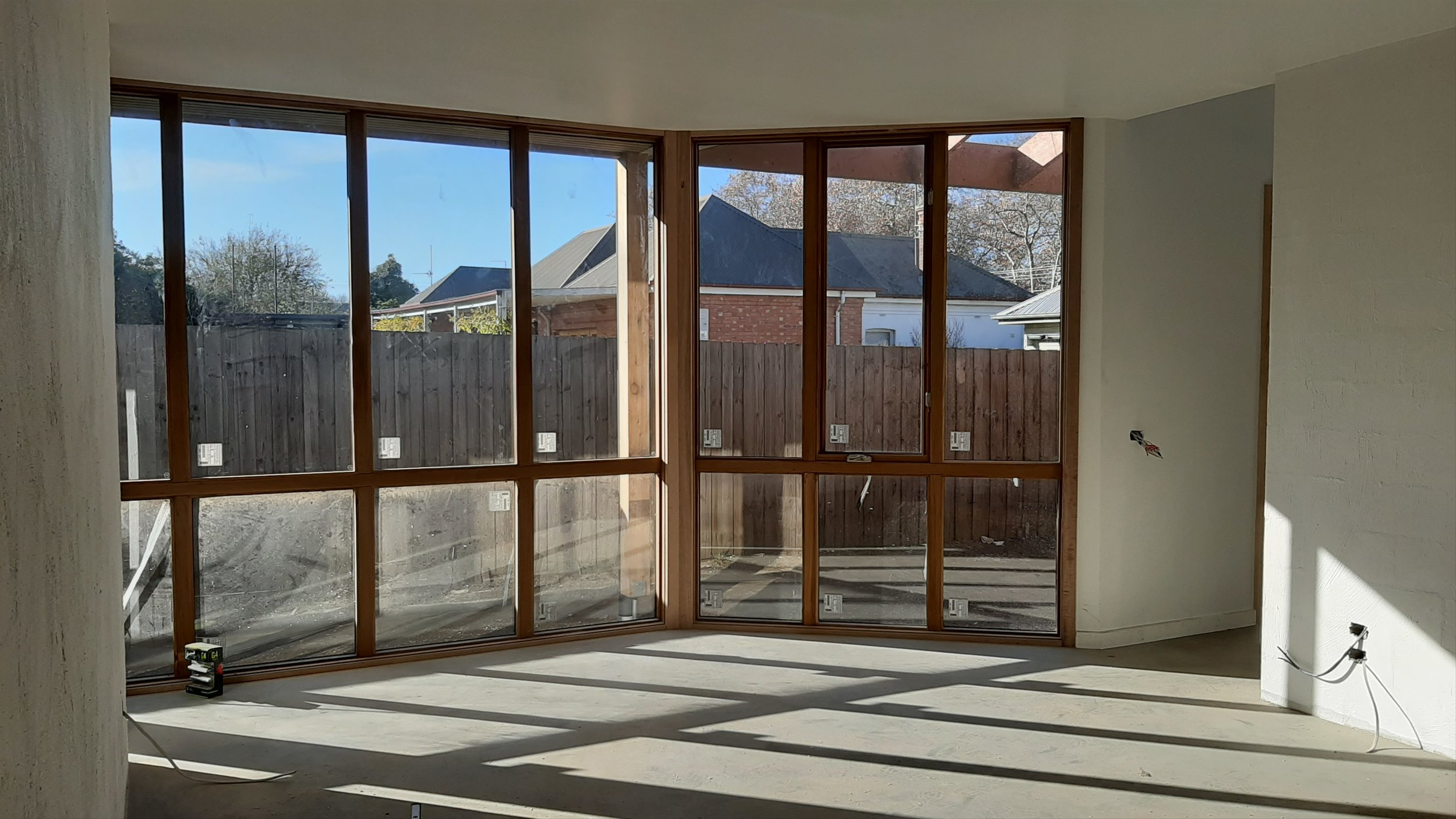 North facing living area with sunlight striking the concrete floor and internal blockwork wall