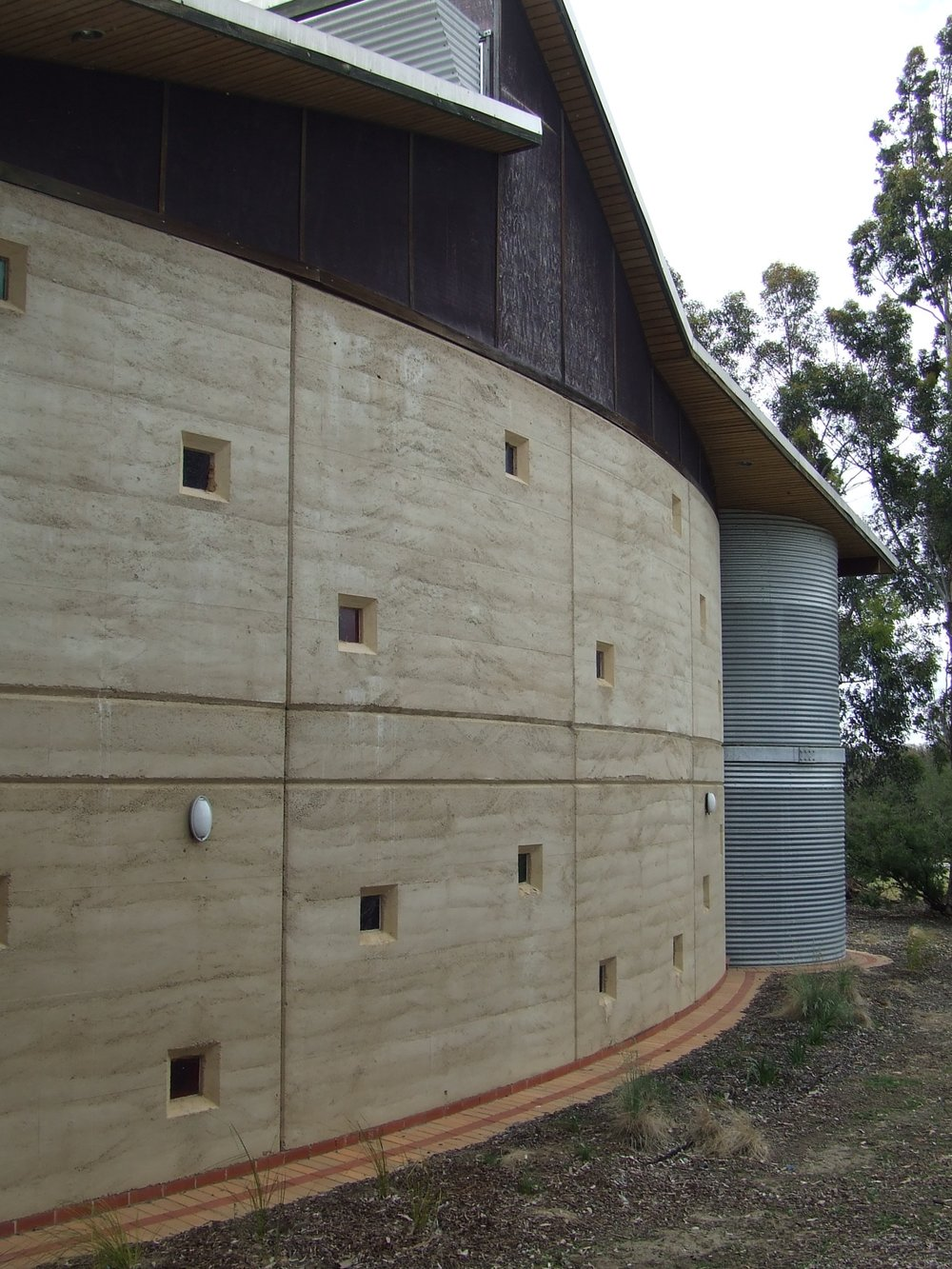 Despite being a monolithic structural element, the rammed earth has been sculpted into plastic and playful forms.