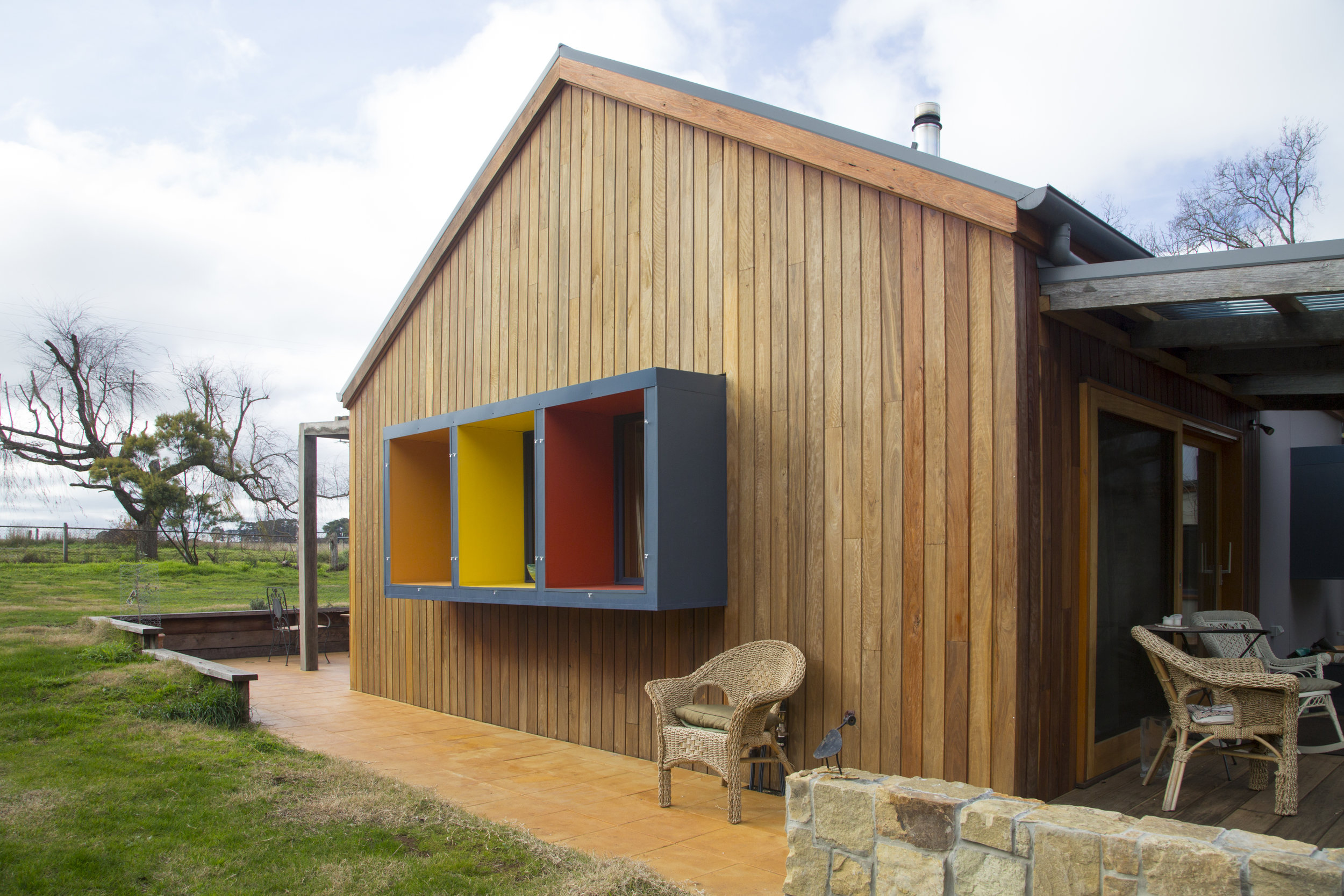 A modern home exterior with bold, bight window frames and stained wood facade designed by Enduring Domain Architecture