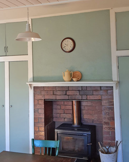 wood heater in brick chimney, country dining room with painted cupboards and lining boards