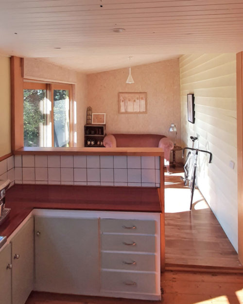 Country kitchen with white tiles, painted cupboard fronts, sun room with painted weatherboards