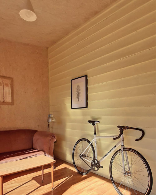 Weatherboard sun room with fixed gear track bicycle