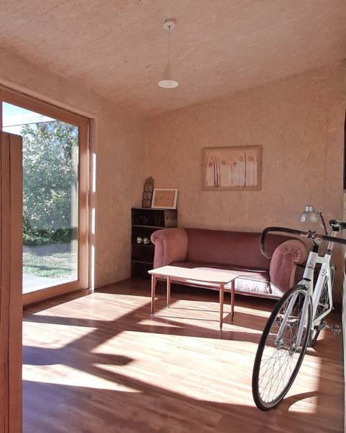 Sun room with passive solar gain, OSB lining, double-stud walls, thick insulation, double-glazing, white Avanti track bike