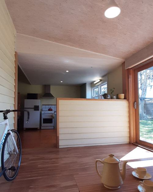 Raked ceiling in sun room with white washed OSB and painted weatherboards